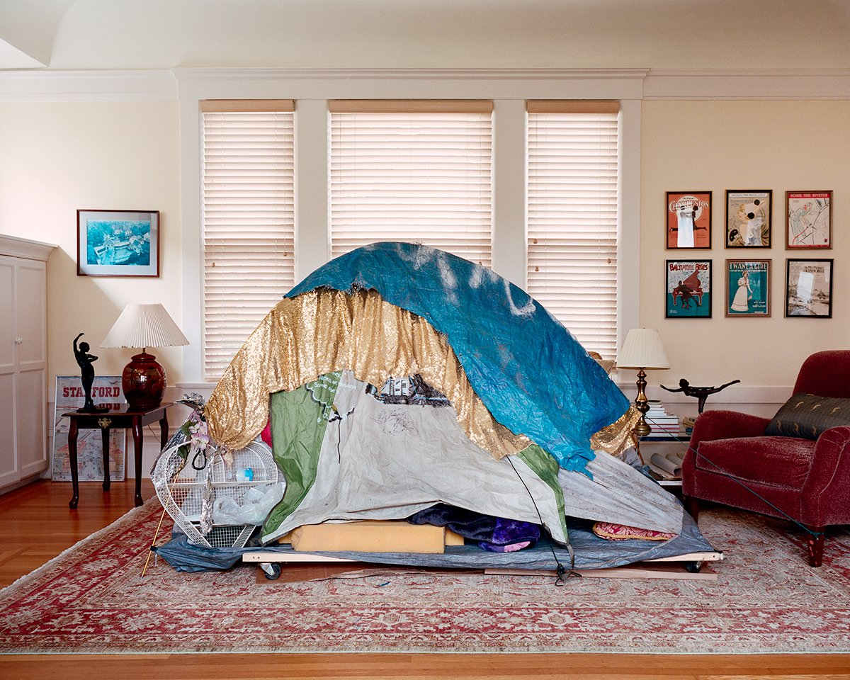 A photo of a tent covered in tarps in the middle of an opulent living room.